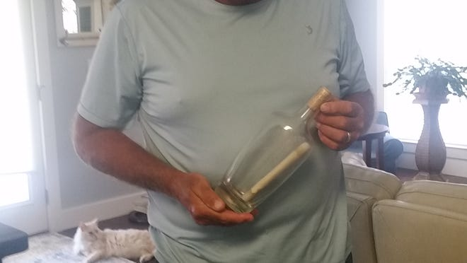 Gary Henrickson holds the message in a bottle he found at a Santa Rosa Beach during Memorial Day weekend.