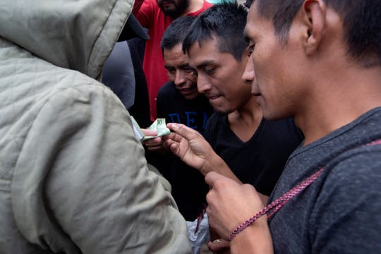 Guatemalan men who were deported from the United States, change money after arriving at the Air Force Base in Guatemala City, Tuesday, July 16, 2019.