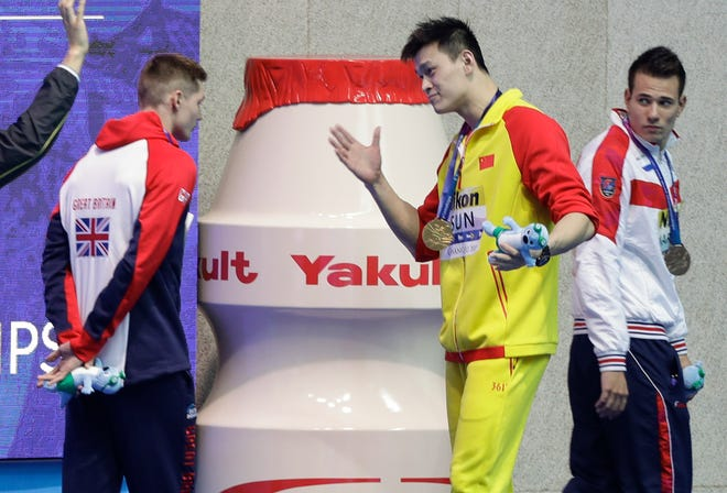 Gold medalist China's Sun Yang, center, gestures to Britain's bronze medalist Duncan Scott, left, following the medal ceremony in the men's 200m freestyle final at the World Swimming Championships.