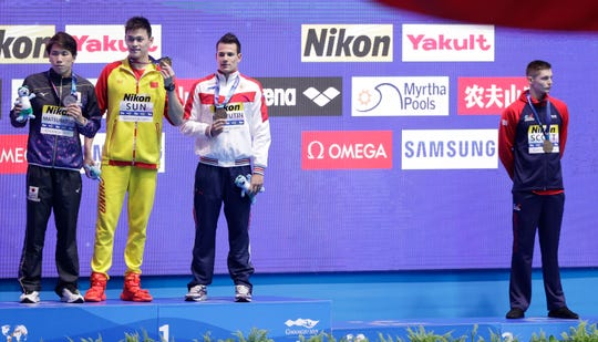 Britain's bronze medalist Duncan Scott, right, refuses to stand with gold medalist China's Sun Yang, second left, as silver winner Japan's Katsuhiro Matsumoto, left, and joint bronze medal winner Russia's Martin Malyutin on the podium.