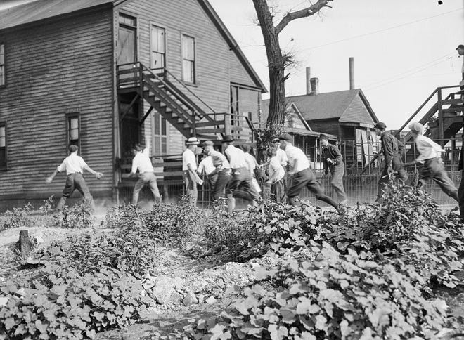 In this 1919 photo provided by the Chicago History Museum, a victim is stoned and bludgeoned under a corner of a house during the race riots in Chicago.
