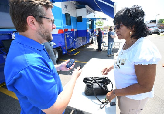 "Kevin Waskelis with DTE public affairs helps Sharon Hughes of Detroit with some phone and tablet charges at the DTE mobile command center in the Kroger parking lot in Royal Oak. Sharon Hughes of Detroit has been out of power since returning Sunday from her cottage in Canada, perhaps earlier.  ""I've been going everyday to the gas station to get ice so when I heard about this, I said that's a good deal, I pay my bill on time, I deserve it.""  Besides getting her phone charged she picked up ice and water as well."
