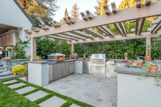 : This Palo Alto, California, outdoor kitchen is housed under a pergola and boasts not only a grill, but an outdoor pizza oven.