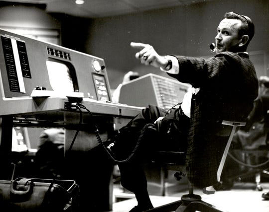 Christopher Kraft, flight director during Project Mercury, works at his console inside the Flight Control area at Mercury Mission Control, in Houston.