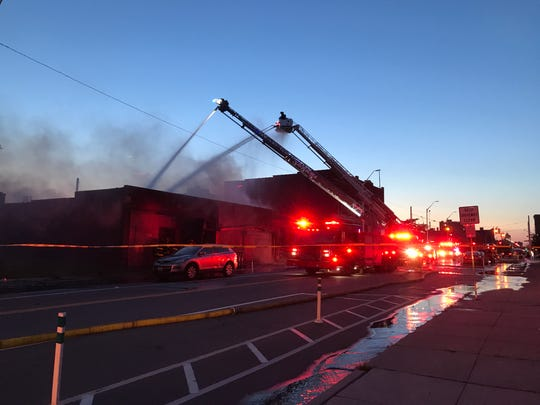 Detroit firefighters battle a blaze at the site of the former Gold Dollar bar on Cass Avenue just north of the Masonic Temple and Little Caesars Arena in Detroit on Monday.
