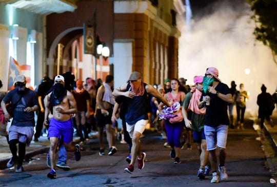Demonstrators affected by tear gas thrown by the police run during clashes in San Juan, Puerto Rico, Monday, July 22, 2019.
