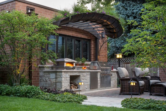 This Chicago-area outdoor kitchen is directly linked to the home, sharing an exterior wall. This design often allows for an easy transition between indoor and outdoor kitchens.