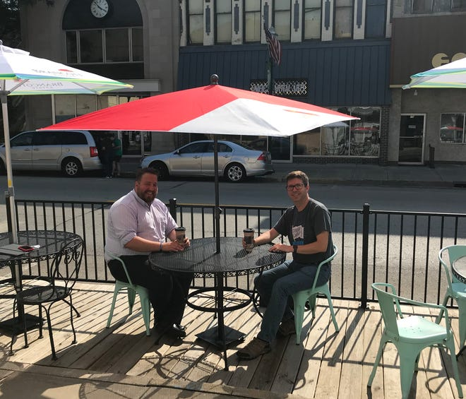 City Council member Ben Giles and President Brian Kolstad gather to drink coffees under new parklet umbrellas at , where the public will soon be able to enjoy drinks.