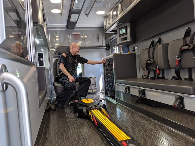 Sandusky County EMS Captain John Marcson demonstrates new seat belts in recently purchased ambulances that allow rescue workers to stay strapped to a seat while assisting patients.
