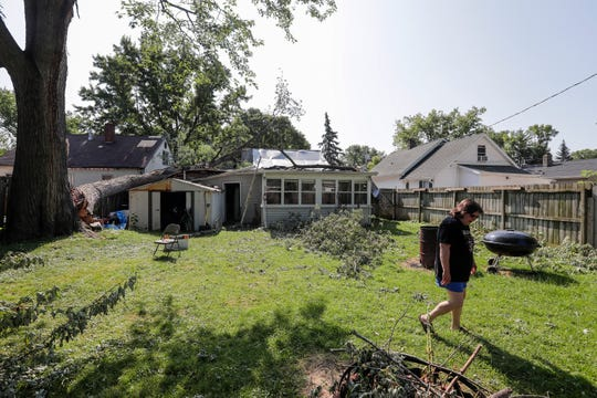 Lisa Belleau walks around the debris in her backyard on the 1000 block of Wirtz Avenue Tuesday, July 23, 2019, in Green Bay, Wis. A large tree fell on her garage during the first storm that ripped through the area on Saturday, taking out a switch that caused her to lose power to half of her house.