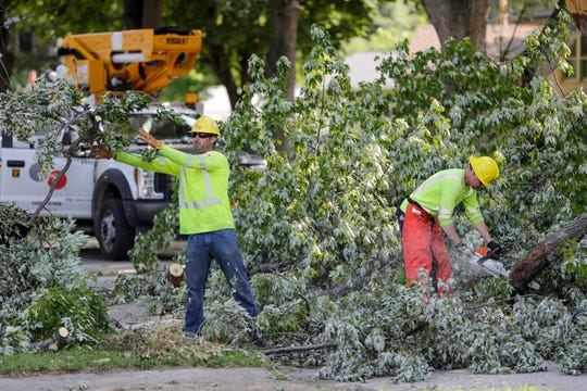 WPS workers cut up a tree in the middle of the street on the 800 block of 13th Avenue Tuesday, July 23, 2019, in Green Bay, Wis.