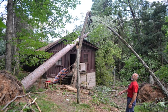 Cliff Pohlheber, program director at Bear Paw Boy Scout Camp near Mountain in Oconto County, surveys the damage after the July 19 storm that damaged several buildings at the camp, including the one pictured, the staff residence with a boathouse on the lower leve. The camp was to be closed until at least Wednesday.