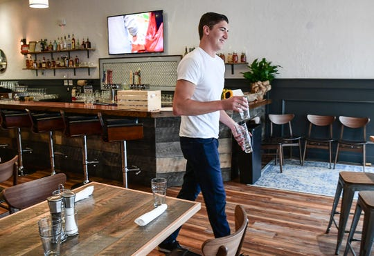 Evolve restaurant waiter Jacob Castle sets tables before lunch at 360 College Avenue in Clemson recently opened.