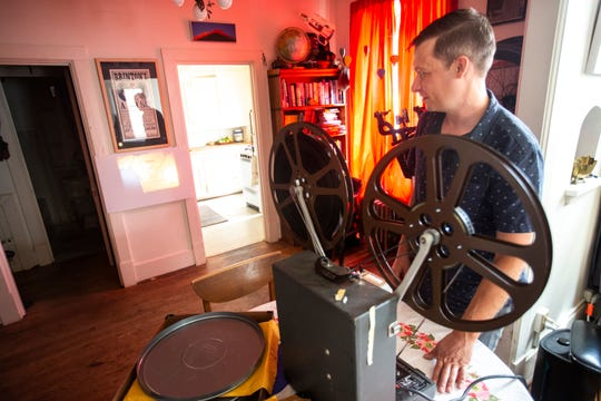 John Richard, a documentary filmmaker, displays a 16mm film from The Iowa Mountaineers, a group founded at the University of Iowa in the 1940s, on a Kodak Pageant 250S reel to reel film projector, Monday, July 22, 2019, at his apartment in the Northside District in Iowa City, Iowa.