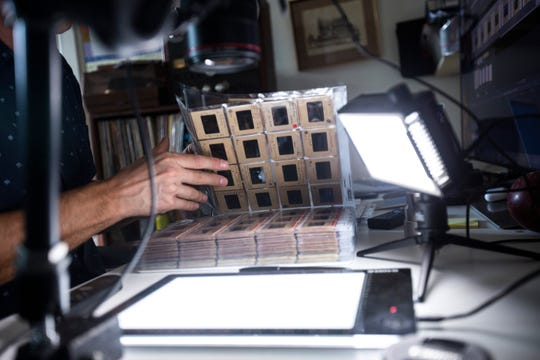 John Richard, a documentary filmmaker, looks through an album of 35mm Kodachrome film photo negatives from The Iowa Mountaineers, a group founded at the University of Iowa in the 1940s, while digitizing the images with his custom setup, Monday, July 22, 2019, at his apartment in the Northside District in Iowa City, Iowa. In addition to the writings from members of The Iowa Mountaineers, the cardboard casing surrounding the film helps Richard to identify an era of when the film was developed.