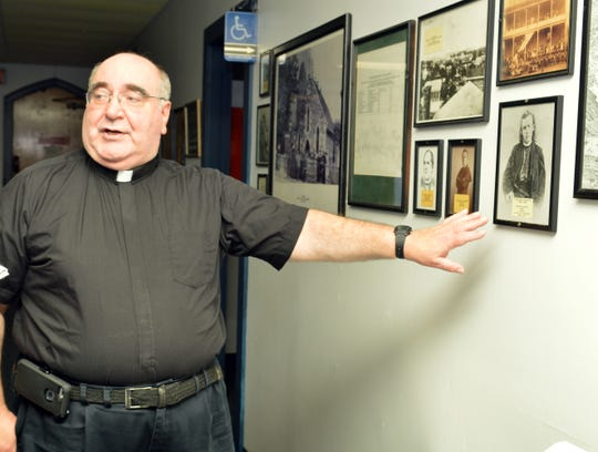 Father Ronald Franco shows a photo of Father Abram Ryan, pastor of Immaculate Conception Parish, 1865-1867.