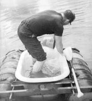 On Aug. 24, 1969, Vic Jackson, a Ludington, Michigan, resident, traveled across Lake Michigan in a bathtub to Manitowoc. Pictured: Jackson bailing the tub.