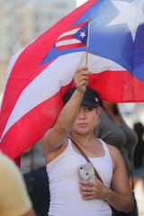 Ineabell Medina, of Milwaukee, holds a flag during the rally.