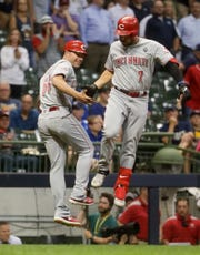 Eugenio Suarez celebrates his two-run home run with third base coach J.R. House in the ninth inning Monday night.