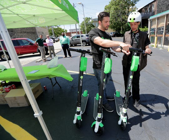 Demetre Frangogiannis. left, a city launcher with Lime, shows Steven Johnson, of Milwaukee how to operate a Lime scooter.
