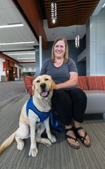 Teacher Sue Bachofen sits with her dog Champ at Mukwonago High School on Monday, July 22, 2019. Champ will be a full-time facility dog at the school.