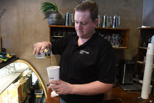Duncan Clayton of Clayton's Downtown Grill pours a beer into one of the carryout cups that ill be used in Mountain Home's new entertainment district.