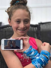 Bianca Marchese, 13, was Mallory Grossman's best friend and came up with the idea of blue bracelets to raise bullying awareness after losing her friend in 2017. She holds a photo of her with Mallory on her cellphone.