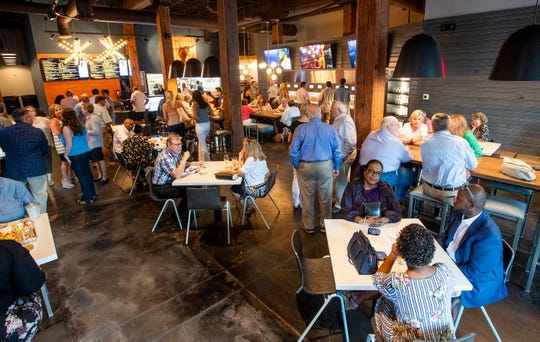 Customers partake of food and drink during a pre opening of the Tower Taproom in Montgomery, Ala., on Monday July 22, 2019.