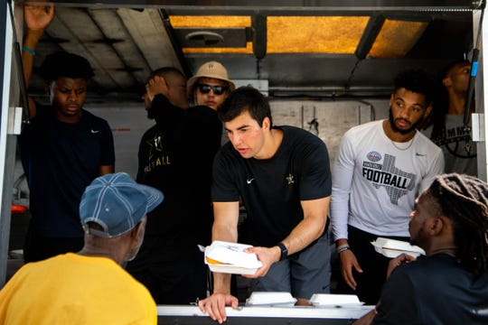 Mo Hasan (center), who founded Second Spoon, works with his teammates in the food truck.
