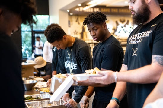 Vanderbilt football players package meals for the homeless at the school's athletic dining facility.