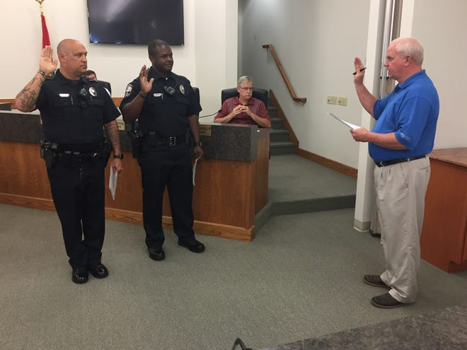 Dickson Mayor Don L. Weiss Jr., right, administers the oath of office to new Dickson Police Department officers, from left, Kenneth Howard and Otis Gerron during the Finance and Management Committee meeting Monday, July 15.