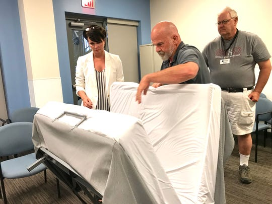 Shelter volunteers Kevin Hostler (center), Barbara Layden and Steve Fulton demonstrate how to assemble new cots at a recent staff meeting regarding the August opening of an emergency shelter at Franklin First United Methodist Church.