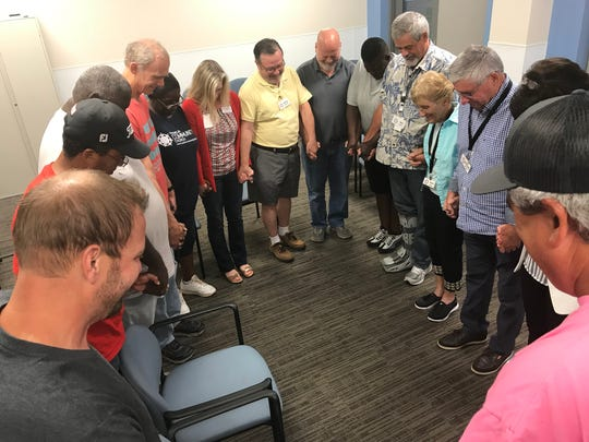 Emergency shelter volunteers take a moment to say a prayer at a volunteer meeting last week, reviewing the procedures to prepare for the shelter's August opening.