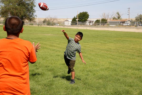 iMPACT Shiprock participants toss a football during a break in activities on July 23 at Shiprock High School in Shiprock.