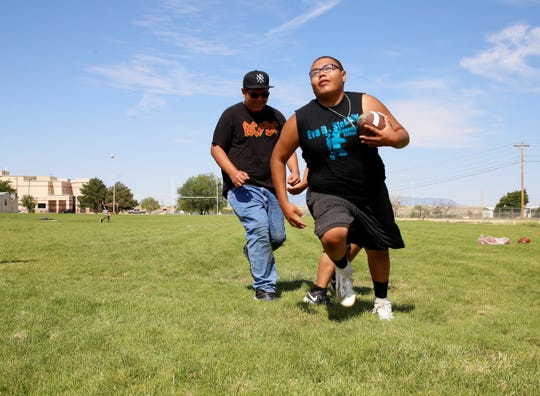 Cudia Tihe runs from group members during a football exercise at iMPACT Shiprock on July 23 at Shiprock High School in Shiprock.