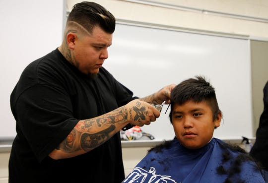 Josh Sandoval with Southwest Barbers gives Caleb Mariano a haircut during iMPACT Shiprock on July 23 at Shiprock High School in Shiprock.