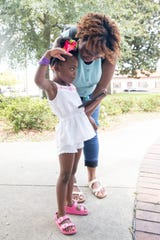 "Aubree Randolph, 4, mimics the airplane action with her hand as she and her mother Tahsaria Randolph watch the ""Top Gun: Maverick"" movie trailer in downtown Pensacola on Tuesday, July 23, 2019."