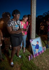 Mother Casey Scott, left, and D'Errica Rodriguez-Schuyler look down at the photograph of 3-year-old Cherish Jackson during the candlelight vigil for her at Bayview Park in Pensacola on Monday, July 22, 2019.  Cherish was shot and killed by her father Terrence Jackson (who also took his own life) this past Saturday.