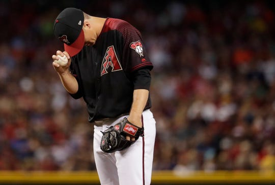 Arizona Diamondbacks starting pitcher Zack Greinke adjusts his cap after giving up a run against the Milwaukee Brewers during the fourth inning of a baseball game, Saturday, July 20, 2019, in Phoenix.