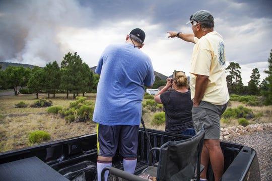 Residentes de la comunidad North Peak observan el humo que sale de las montañas, por el incendio.