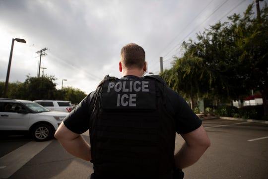 Un agente de ICE supervisa una protesta pro-inmigrante en Escondido, California.
