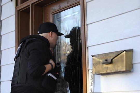 Un agente de ICE mira a través de una puerta esperando que le abran, durante el operativo migratorio llevado a cabo en N.Y.