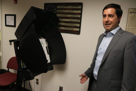 Ohio Secretary of State Frank LaRose checks out one of the new voting machines implemented by the Ottawa County Board of Elections during a tour and discussion regarding cybersecurity.