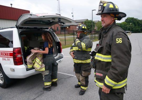From left, Pleasant Valley Fire Department firefighter EMT Melissa Lawlor, comissioner Ken Luby and firefighter EMT John Hopper prepare to receive instructions on how to properly decontaminate their turn out gear on July 11, 2019.