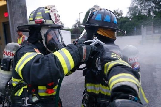 Hyde Park Fire Department firefighter Alex Wilcha decontaminates fellow firefighter Roger Lambert's turnout gear during training on July 11, 2019.