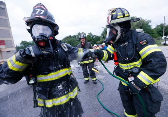 Hyde Park Fire Department firefighter Alex Wilcha decontaminates fellow firefighter Roger Lambert's turnout gear during training on July 11, 2019.