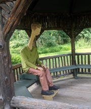 "Hans van Meeuwen's sculpture ""Melvin"" is casually seated inside on of the rustic gazebos at Wilderstein Historic Site."
