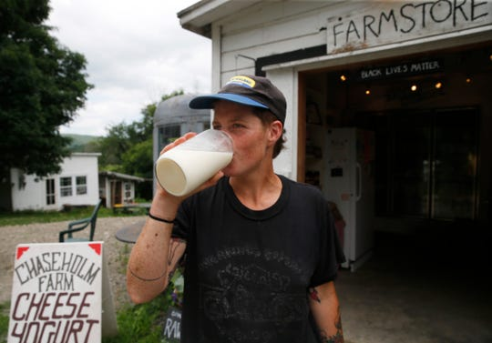 Before heading to New York City for a farmers market, Sarah Chase has some milk at Chaseholm Farm in Pine Plains on July 12, 2019.