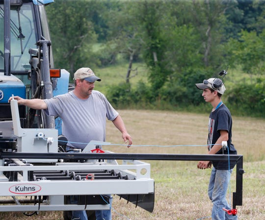 """Tom  """"Tiger"""" Wagner and his step-son Andrew work with a  tie grabber, which is a piece fo equipment that gathers hay bales during hay harvesting at Hahn Farm in Salt Point on July 11, 2019."""