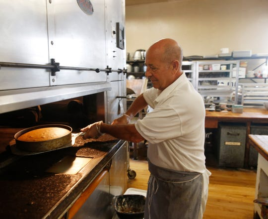Caffe Aurora owner Lou Strippoli pulls a cake from the oven at the cafe in the City of Poughkeepsie on July 23, 2019.